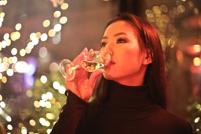 Asianwoman drinking glass if wine